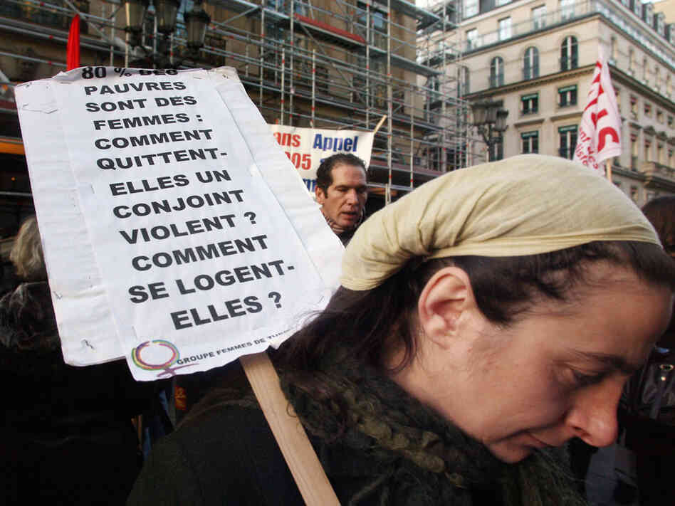 A woman holds a banner which refers to poor, powerless women facing domestic violence.