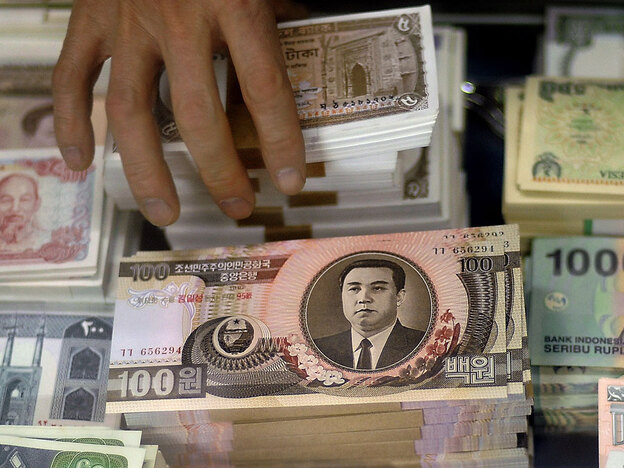 A currency trader arranges a stack of old North Korean bank notes featuring an image of the country's founder, Kim Il Sung, amid bundles of other foreign bills at a trade market in Beijing.