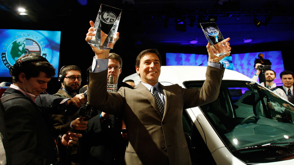 Ford Motor Co. President of the Americas Mark Fields holds up the 2010 North American Truck of the Year award and Car of the Year award Monday at the North American International Auto Show in Detroit.