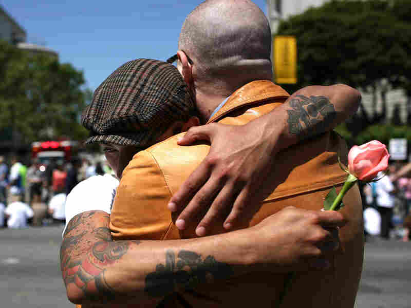 Shawn Higgins (right) and his partner Robert Franco hug
