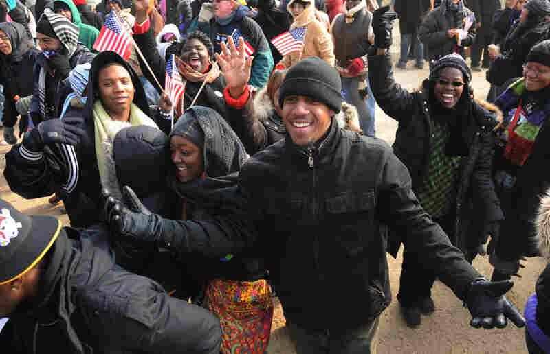 People celebrate at the Washington Monument as BarackObama takes the oath of office, January 2009.