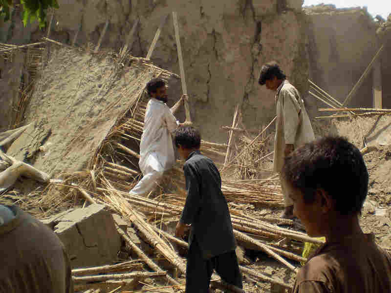 Pakistani villagers gather at the rubble of houses belonging to supporters of Baitullah Mehsud.