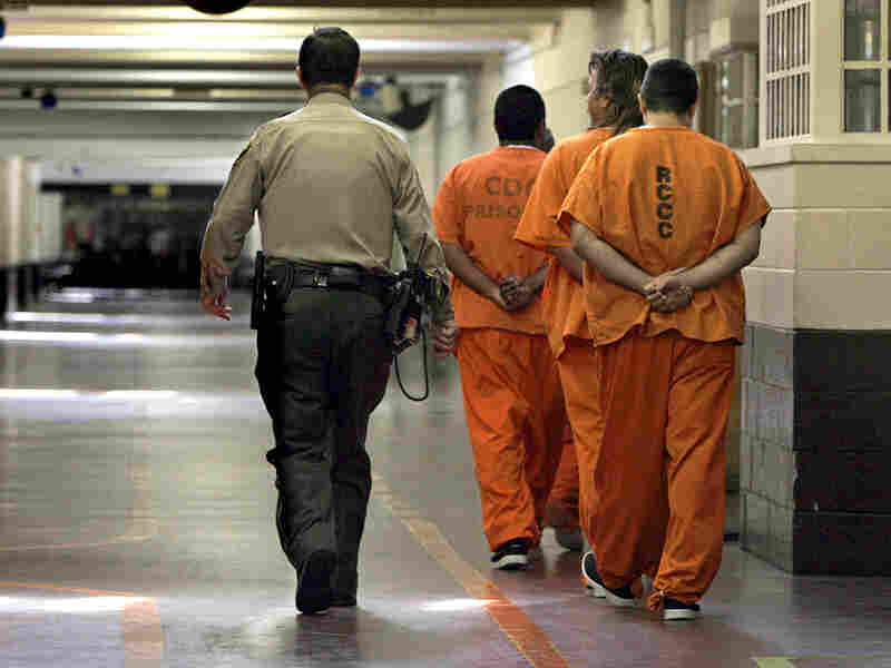 an officer escorts a group of recently arrived prison inmates