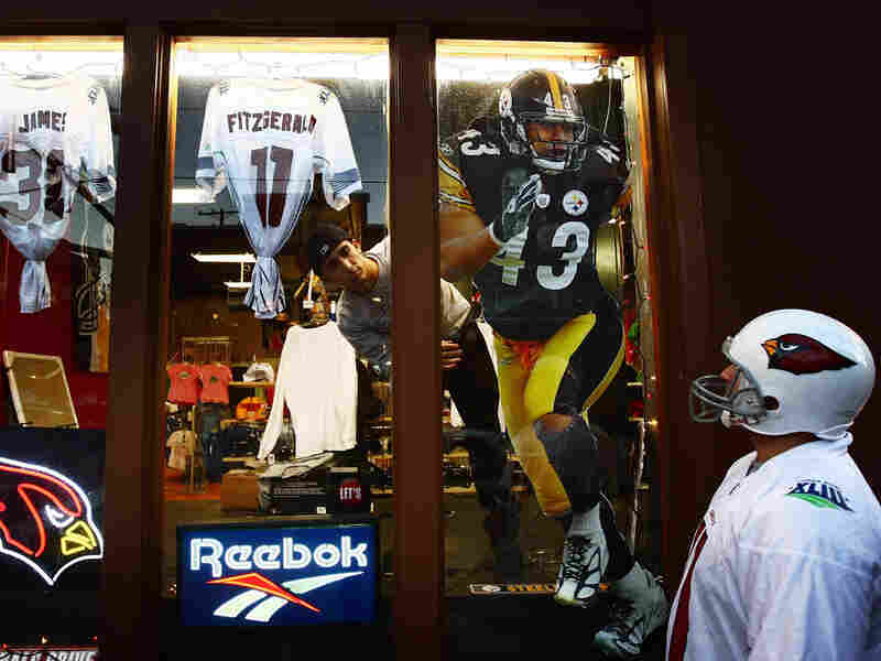A fan gazes at Super Bowl XLIII merchandise in a Tampa, Fla. store window.