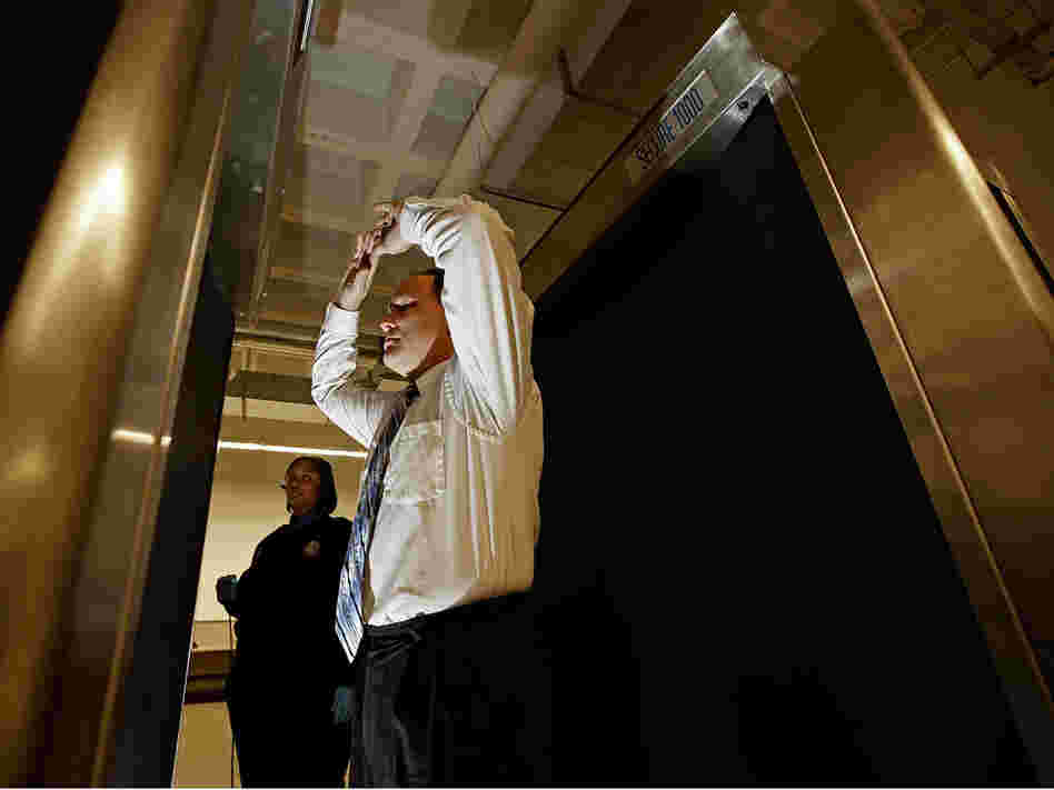 A man stands inside a backscatter scanner at Ronald Reagan National Airport.