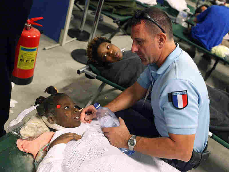 An injured girl is given water by a French aid worker
