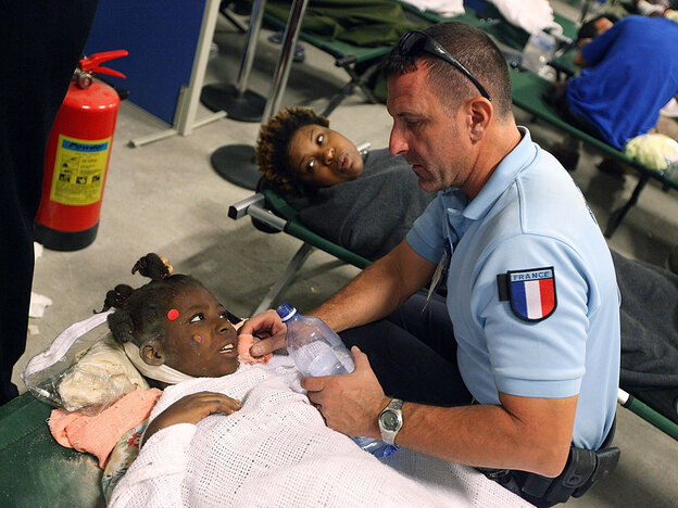 An injured girl is given water by a French aid worker at a makeshift field hospital in Port-au-Prince, Haiti, on Wednesday.