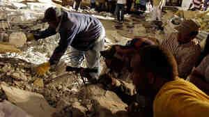 Rescuers peer into rubble in Port-au-Prince, Haiti