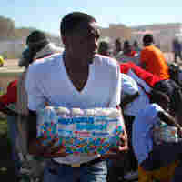 Haitians jostle and shove over a cache of water dropped off by a helicopter. David Gilkey/NPR