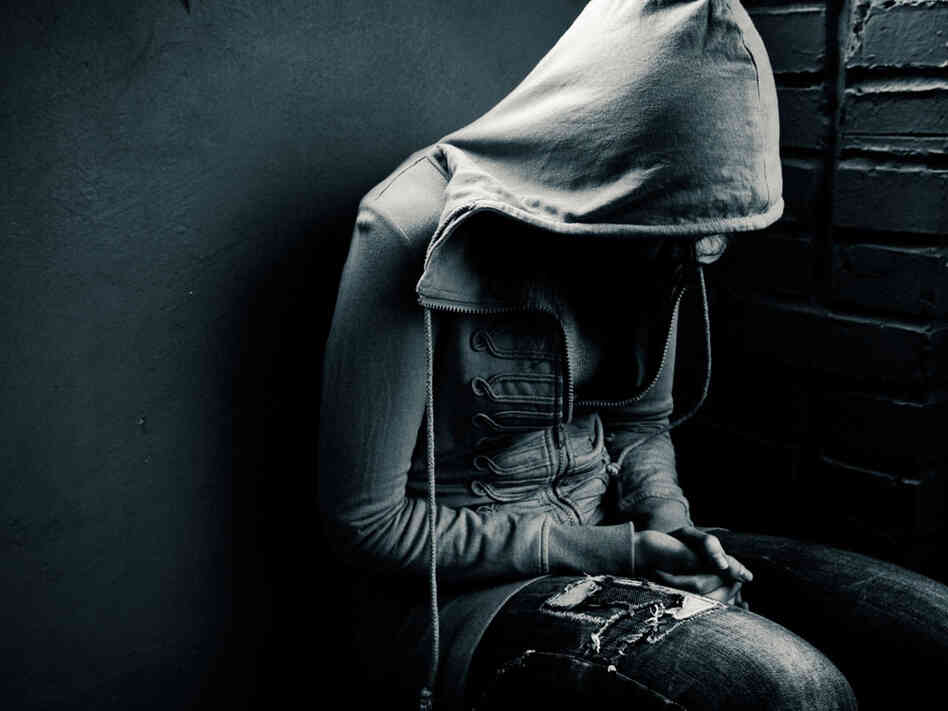 A teen with her headed covered by a hooded sweatshirt.