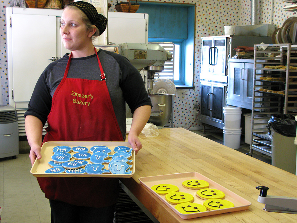 Rachel Murdock displays a tray of Colts cookies at Zinszer's Cookies in Anderson, Ind.