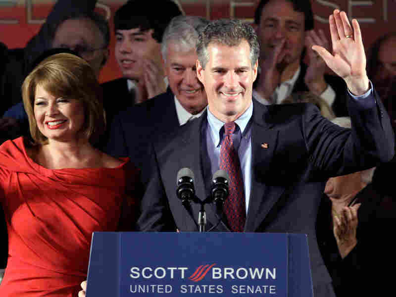 Scott Brown waves from behind a lectern, celebrating his victory.