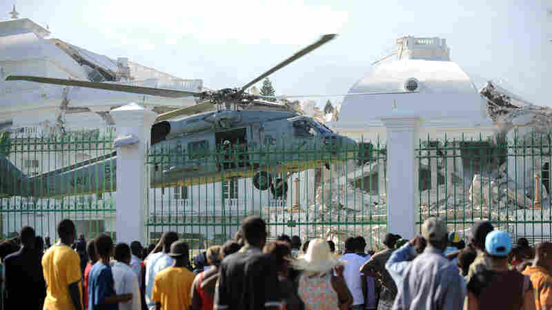 Haitians watch as a U.S. Navy helicopter lands at the presidential palace in Port-au-Prince.