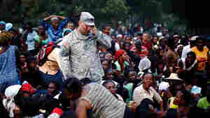 A U.S. Army soldier from the 82nd Airborne Division is surrounded by Haitians.