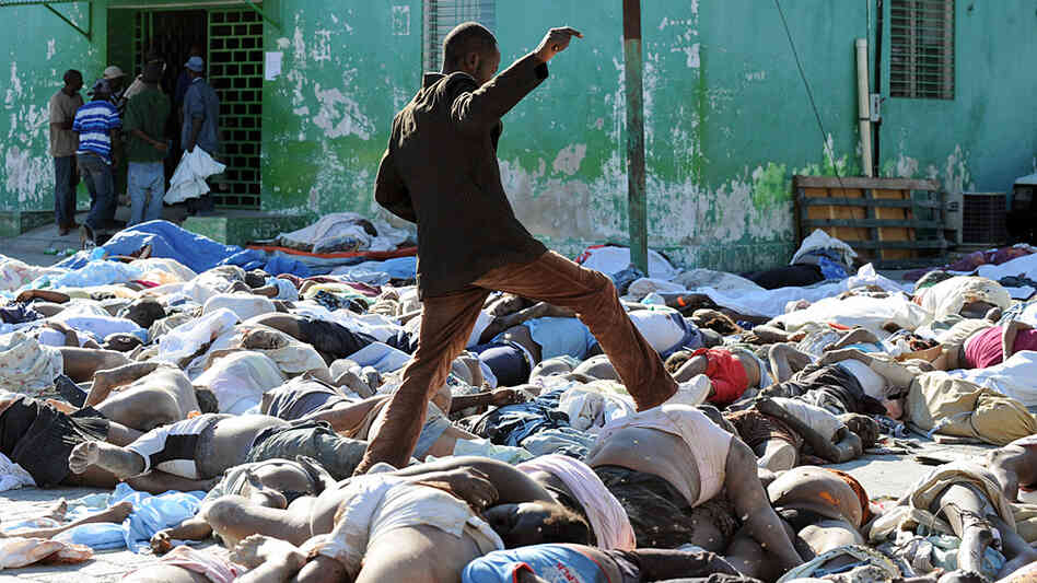 A photo of a Haitian man walking through a make-shift morgue in the aftermath of last week's earthqu