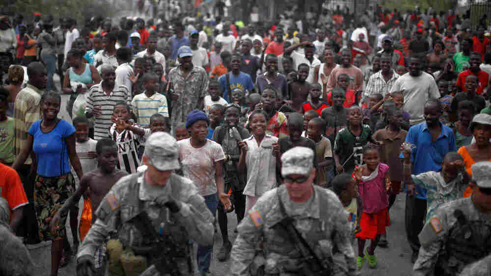 Haitians follow soldiers with the 82nd Airborne division through a street in Port-au-Prince.