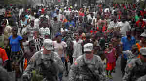 A crowd of Haitians follows soldiers with the 82nd Airborne division down a street in Port-au-Prince