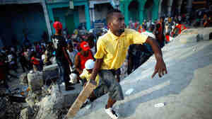 Violence erupts as Haitians loot around a collapsed grocery store
