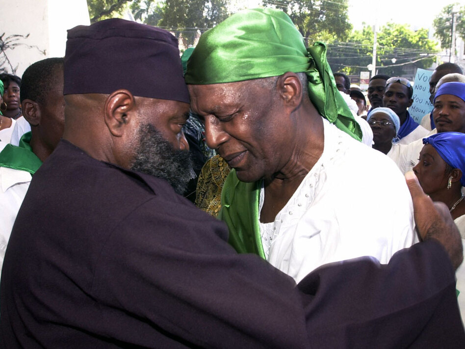 Voodoo priest Max Beauvoir (right) and another man pray in December 2008 during a Voodoo demonstration in Port-au-Prince against sectarianism, neocolonialism and the presence of the U.N. in Haiti. Scholars believe that Voodoo is a derivative of African religions thought to be over 10,000 years old. (AFP/Getty Images)