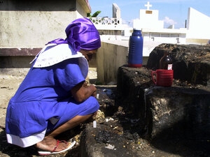 A Haitian woman observes a moment of silence after putting coffee and beer at the grave of her family during celebrations of the Day of the Dead in November 2006.  The two-day celebration honors ancestors by visiting their graves and bringing their favorite foods and drinks.