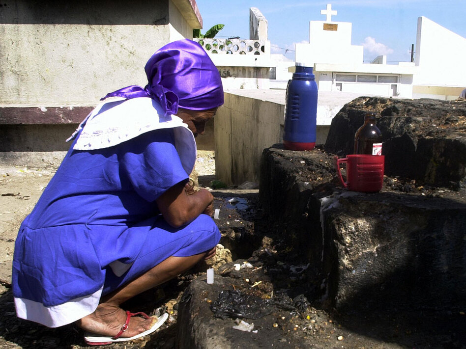 A Haitian woman observes a moment of silence after putting coffee and beer at the grave of her family during celebrations of the Day of the Dead in November 2006.  The two-day celebration honors ancestors by visiting their graves and bringing their favorite foods and drinks. (AFP/Getty Images)