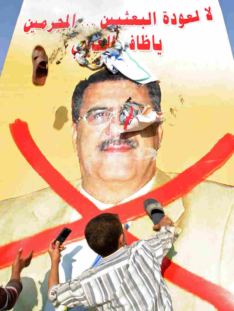 An Iraqi boy uses a shoe to hit a poster of Iraqi lawmaker Dhafir al-Ani in Najaf.