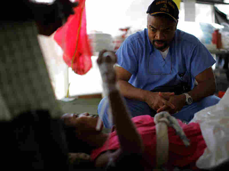 Dr. Henri Ford, a U.S. citizen born in Haiti, speaks in Creole to  an anxious patient.