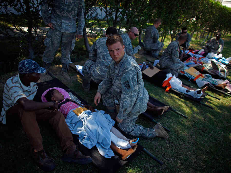 U.S. soldiers watch over patients in a staging area in front of the National Palace.