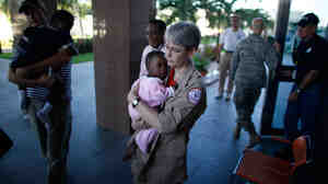An orphaned baby is carried into the American embassy in Port-au-Prince.