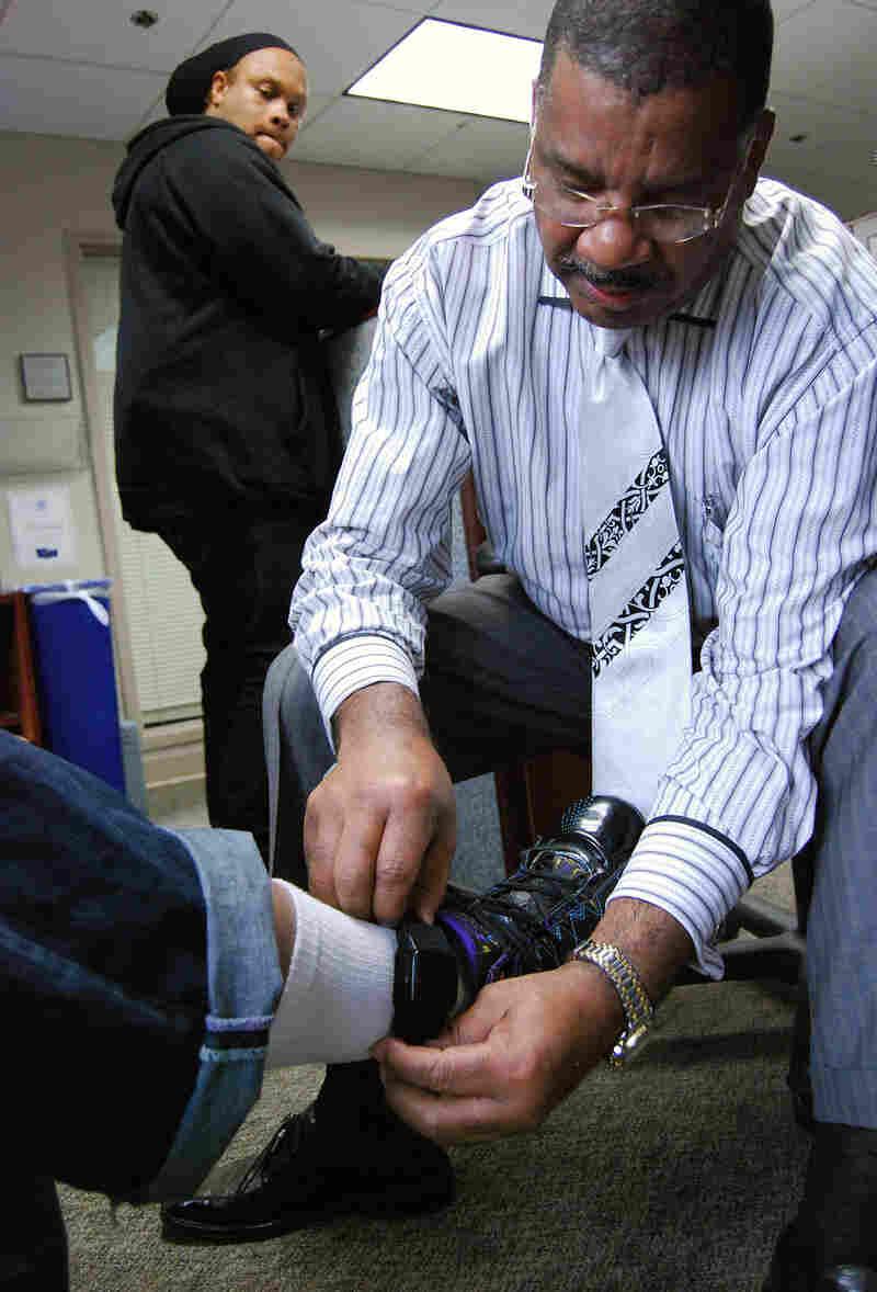 A program manager for the D.C. Pretrial Services Agency adjusts a defendant's ankle bracelet.