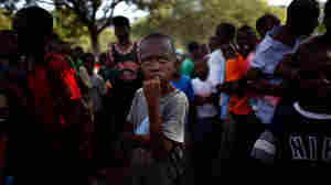 Men, women and children line up to receive water and food rations in Port-au-Prince.