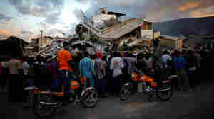Haitians watch the L.A. County Search and Rescue working at a collapsed building in Port-au-Prince.