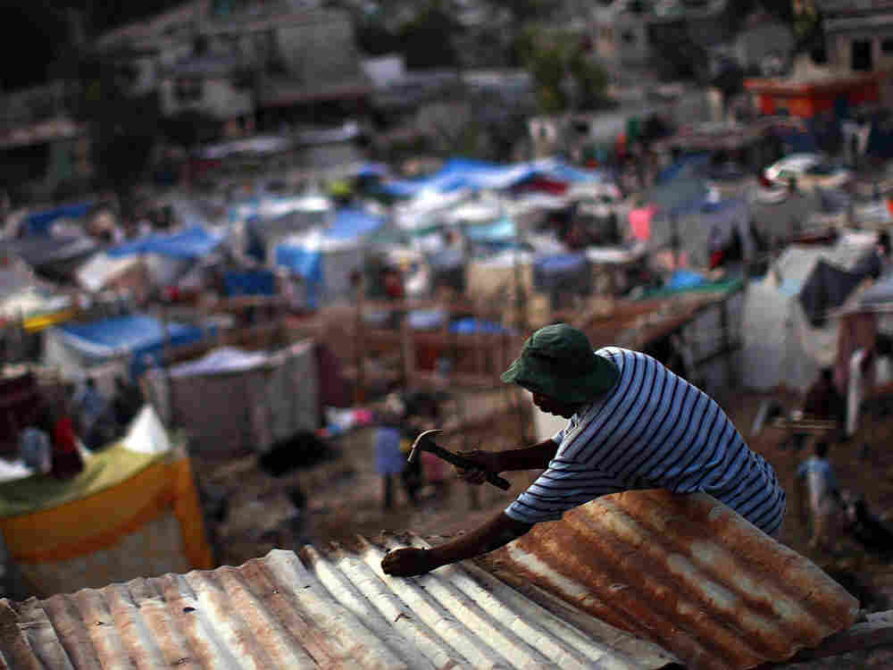 A Haitian man nails a corrugated roof to a temporary structure