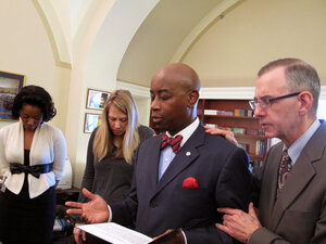 Chaplain Barry Black prays with his staff before delivering the prayer to the Senate