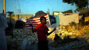 A Haitian boy stands amid rubble in a displacement camp