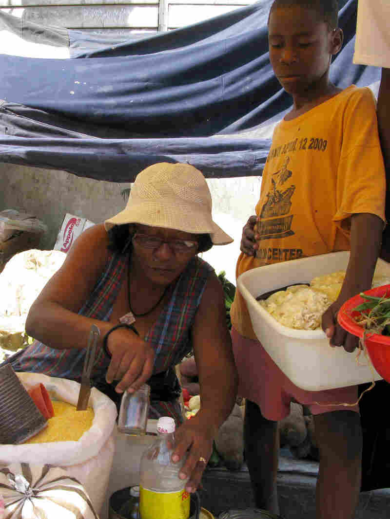 Vendor Vella Pierre sorts through her grain supply on the street in Port-au-Prince