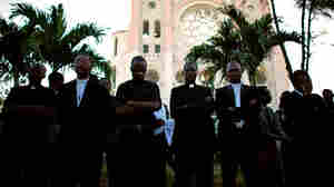 Haitian priests listen to the service for the two clergymen in front of the destroyed cathedral.