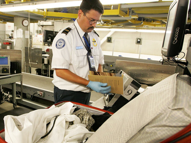 A TSA worker searches a bag at Oakland International Airport.