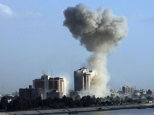 Smoke rises into the sky following one of three explosions near Baghdad hotels.