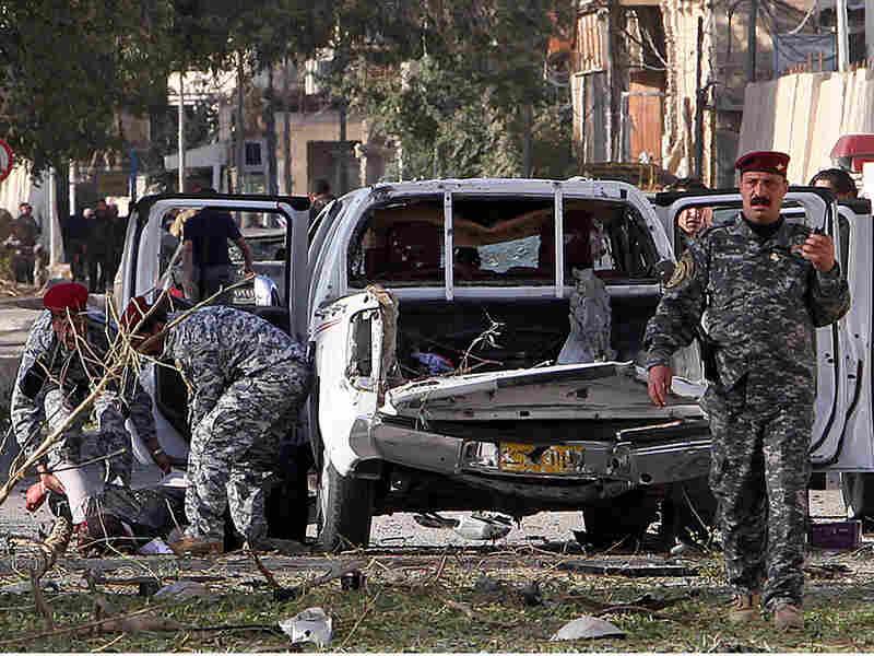 Iraqi police evacuate a victim of bomb attacks in Baghdad.
