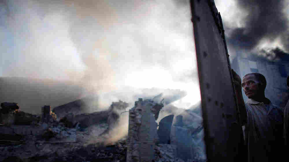 A man stands next to smoldering building in downtown Port-au-Prince, Jan. 18, 2010