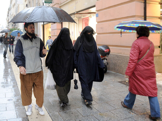 Two veiled Muslim women walk down a street in Marseille, in southern France.