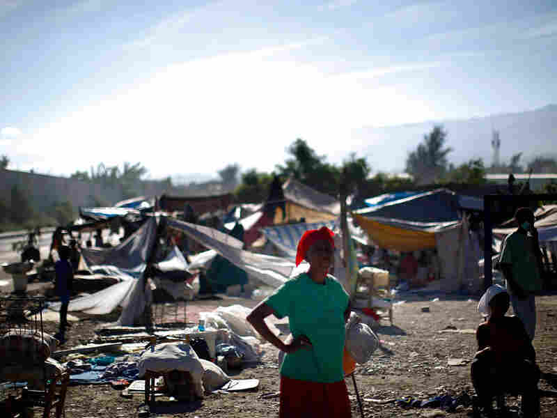A woman stands near a makeshift refugee camp near downtown Port-au-Prince