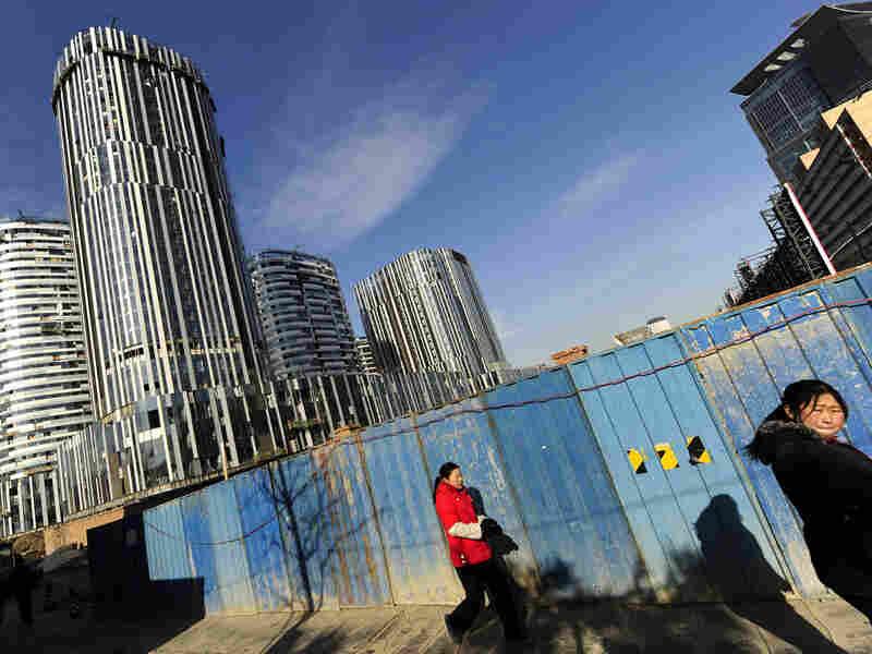 Pedestrians pass a high-rise building being constructed in Beijing