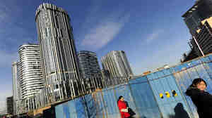 Pedestrians pass a high-rise building being constructed in Beijing