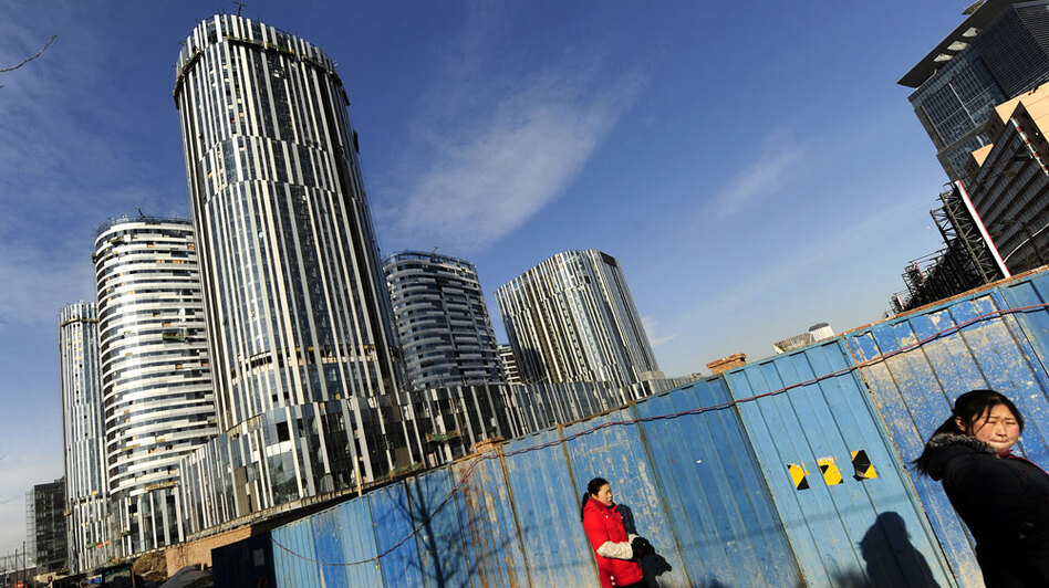 Pedestrians pass a high-rise building being constructed in Beijing in December. New figures show that property sales in China jumped 75 percent last year, as record levels of bank loans boosted purchases.