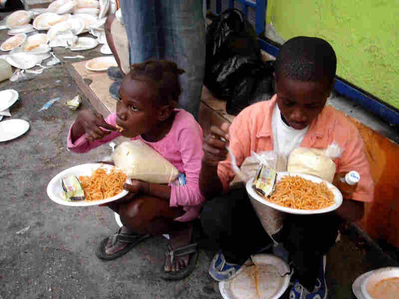 Children eat a free spaghetti meal at Muncheez restaurant in Petionville, Haiti