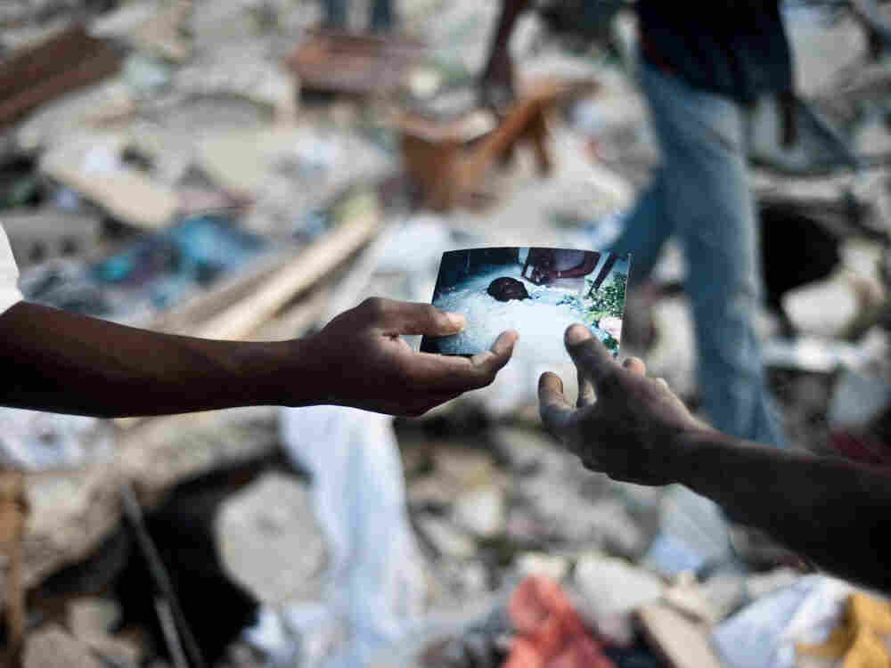 Sorting through the rubble. Haitians look at a photo they found in a collapsed building in Port-au-P