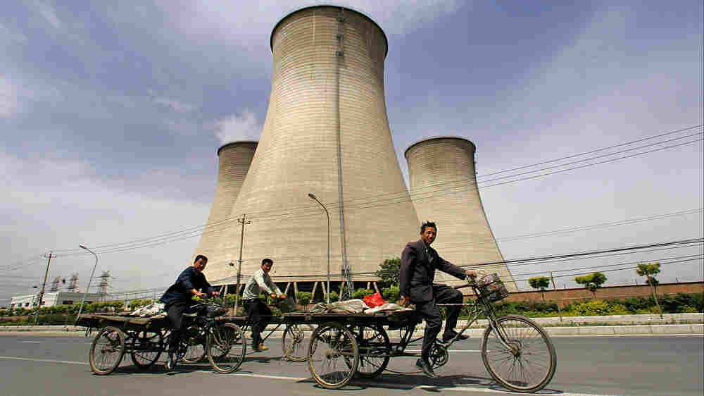 Workers in China bicycle past cooling towers of a coal-fired power plant.