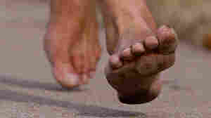 A close up of a barefooted runner's foot.